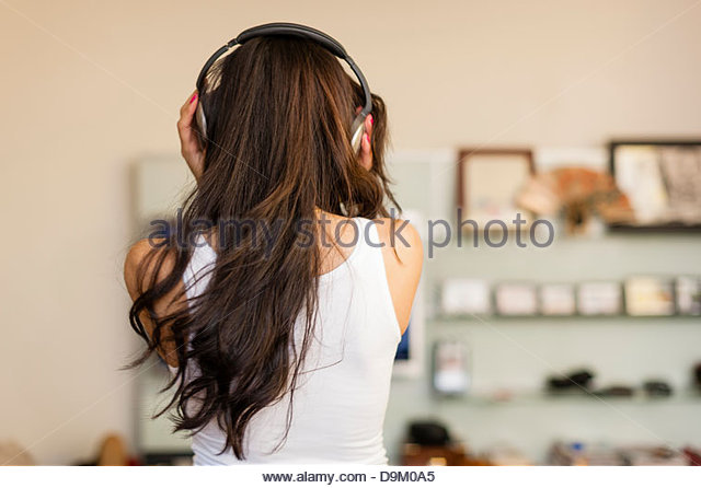 Mid adult woman wearing headphones and dancing, rear view - Stock Image