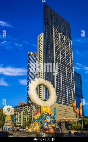 'The Guardians' sculpture by Simon Rigg, against skyscrapers, Southbank Melbourne, Australia. Ceramic tiles, - Stock Image