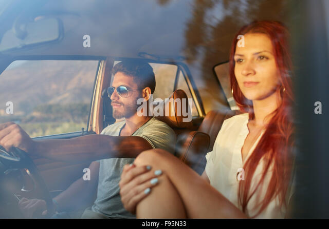 Outdoors shot of a young couple on road trip. Man driving are on summer day with his girlfriend. - Stock-Bilder
