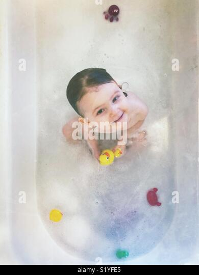 Toddler girl having a bubble bath looking at camera and holding rubber ducks - Stock Image
