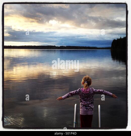 A girl standing at the end of a pier at a huge still lake in Scandinavia - Stock Image