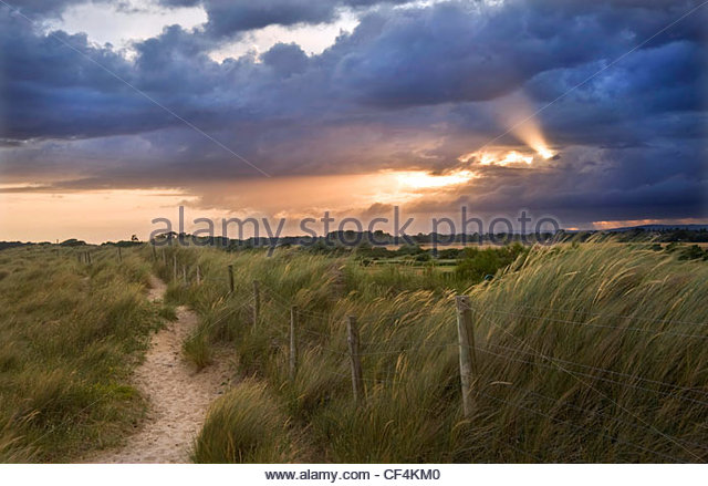 Sunlight bursting through stormy clouds over the South Downs near Littlehampton. - Stock Image