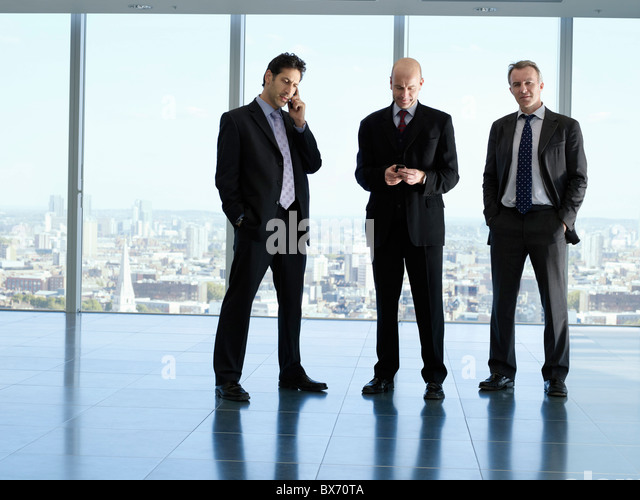 Three executives on mobile phone in empty office space, city landscape in background - Stock Image