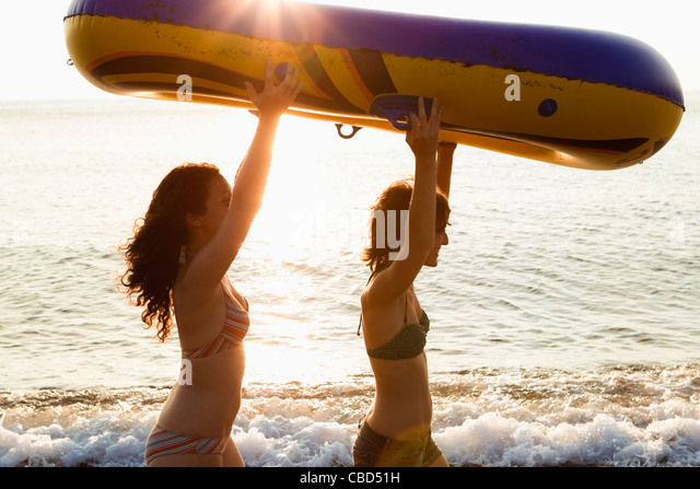 Women carrying inflatable boat on beach - Stock Image