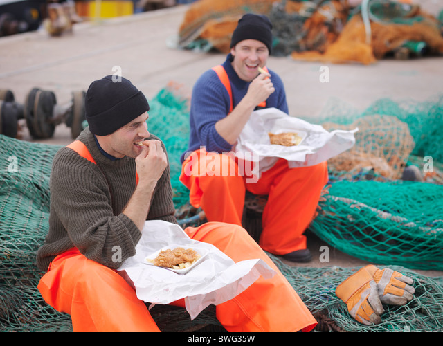 Fishermen eating fish and chips - Stock Image