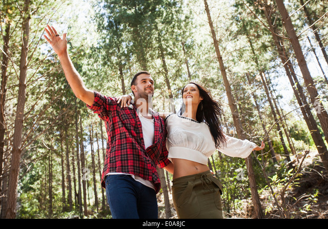 Young couple fooling around in forest, arms outstretched - Stock-Bilder