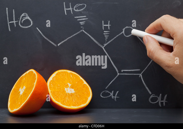 Hand drawing structural formula of vitamin C on blackboard with oranges in front - Stock Image