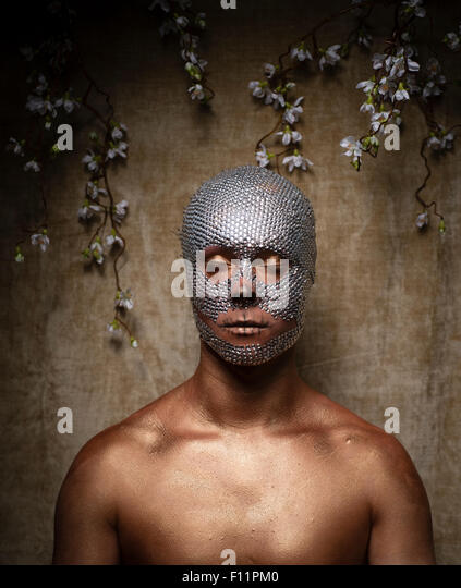 'Day of the Dead' theme portrait - a young man with crystal sequins glued to his face and with his eyes - Stock Image