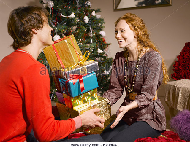 Man giving wife pile of Christmas gifts - Stock Image