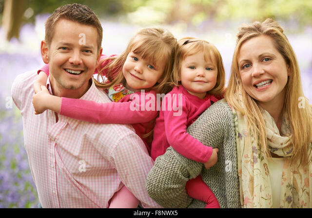 Family Walking Through Bluebell Woods Together - Stock Image