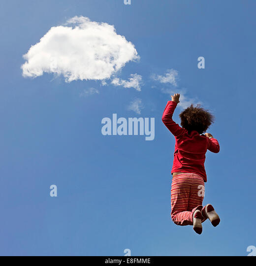 Spain, Catalonia, Provincia de Barcelona, Valles Occidental, Senmanat, Little girl (4-5) jumping and touching piece - Stock Image