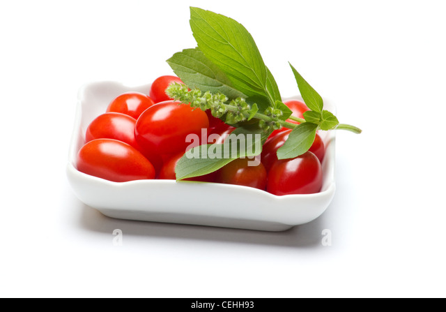 Fresh tomatoes and a sprig of basil in a white background. - Stock Image