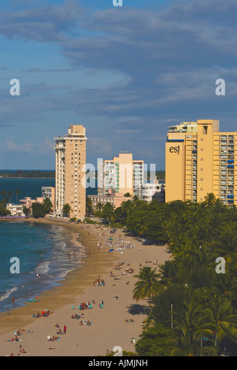 aerial San Juan Puerto Rico Isla Verde beach with sunbathers, blue sky and resort hotels in background, plam trees - Stock Image