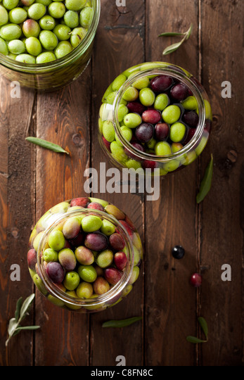 Olives in Brine (with Water and Salt in Glass Jars) on Wood - Stock Image