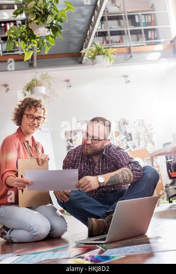 Design professionals discussing proofs at laptop on office floor - Stock-Bilder