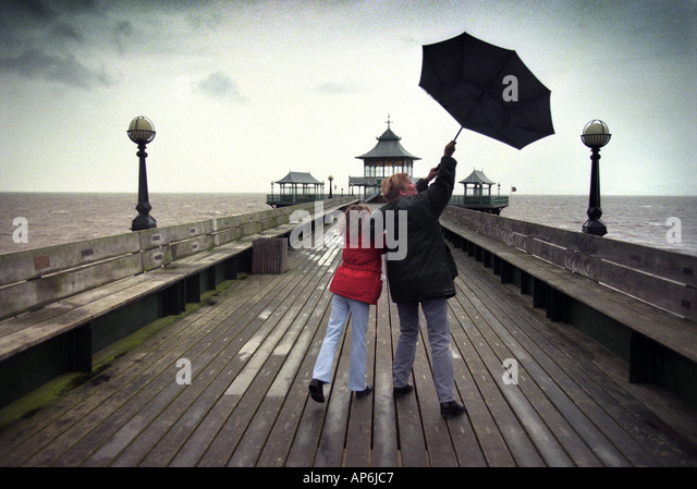 A GIRL AND HER MOTHER STRUGGLE WITH A BLACK UMBRELLA DURING A WALK ON CLEVEDON PIER NORTH SOMERSET UK - Stock Image