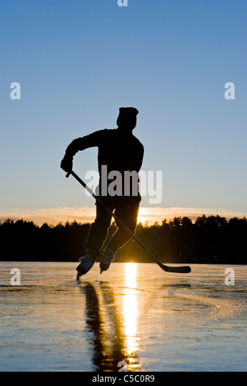 Low angle view of a teenage boy playing ice hockey against clear blue sky at sunset - Stock Image