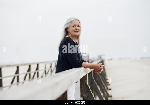 Portrait confident senior woman leaning on beach boardwalk railing - Stock Image