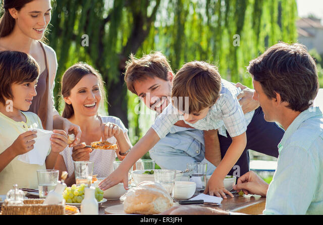 Family enjoying breakfast together outdoors - Stock Image