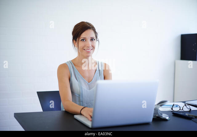 Portrait mid adult woman working from home on laptop - Stock Image