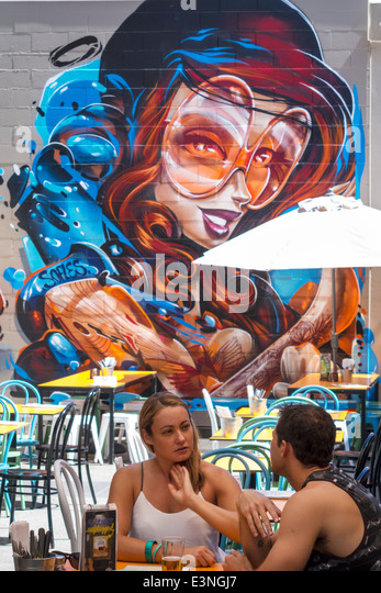 Australia Queensland Brisbane Fortitude Valley restaurant wall mural art man woman couple tables - Stock Image
