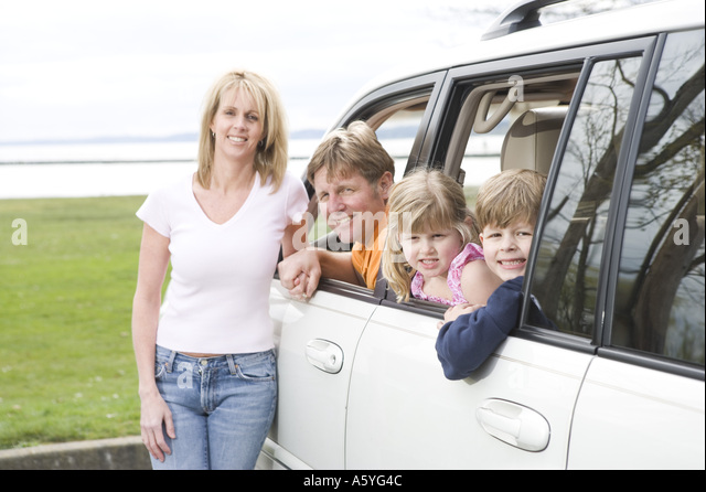 Happy family together in minivan - Stock Image
