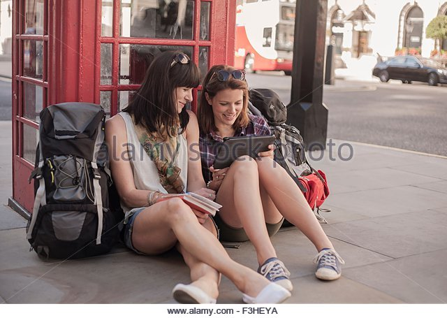 Two women backpackers sitting on sidewalk planning route on digital tablet, London, UK - Stock Image