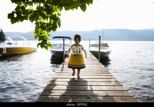 Female toddler exploring pier, Silver Bay, New York, USA - Stock Image