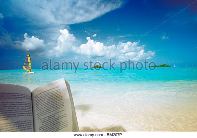 Reading book on the beach, windsurfing and islands in the distance, the Maldives, Indian Ocean - Stock Image