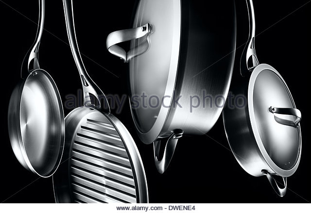 different shape and sizes aluminum stainless steel pots and pans shot in a moody edgy light against black background - Stock Image