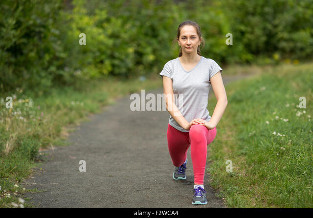 Young sporty girl is warming up outdoors. A healthy lifestyle. - Stock-Bilder
