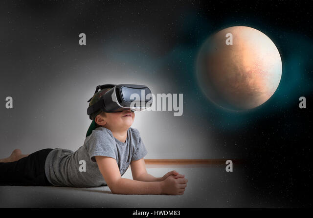 Young boy lying on floor, wearing virtual reality headset, looking at planet, digital composite - Stock-Bilder