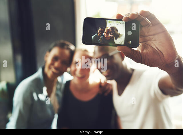 Multi ethnic friends taking a selfie with a phone - Stock Image