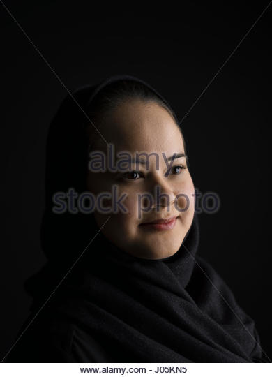 Portrait smiling Middle Eastern woman wearing black hijab looking away against black background - Stock Image