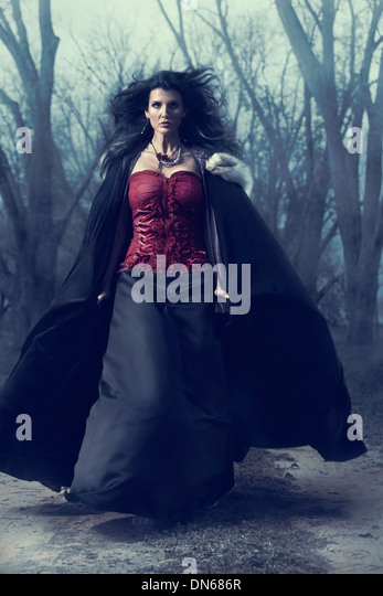 Woman running through wooded path in the fog dressed in Victorian style dress with cape - Stock-Bilder