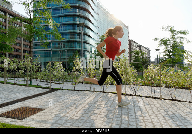 Young woman running past office buildings - Stock-Bilder