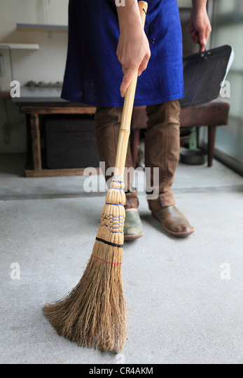 Young Woman Sweeping Room with Broom - Stock Image