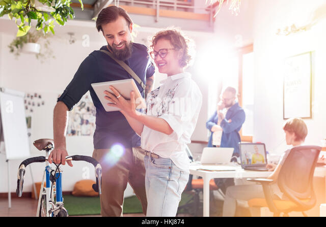 Smiling design professionals with bicycle and digital tablet talking in office - Stock-Bilder