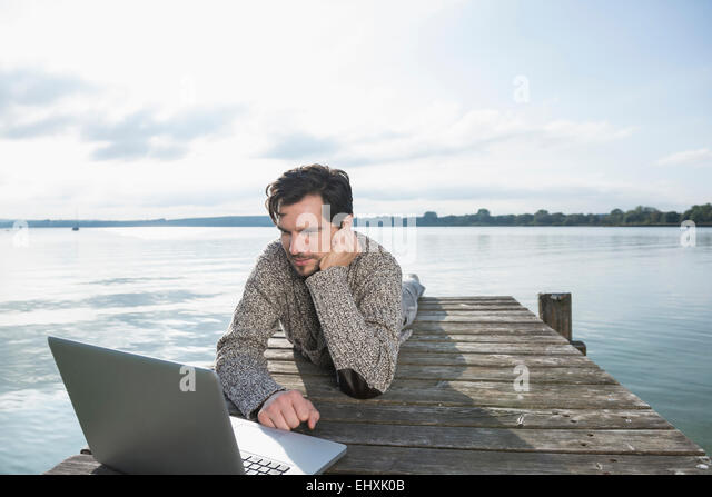 Young man lying on wooden jetty lake laptop - Stock-Bilder
