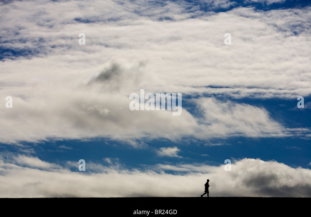 One man running a marathon with blue skies and white clouds above him in Lincoln, Nebraska (Silhouette). - Stock Image