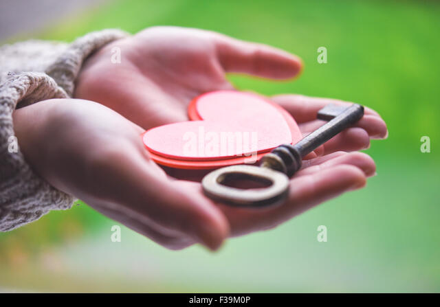Woman holding a heart and a key - Stock-Bilder