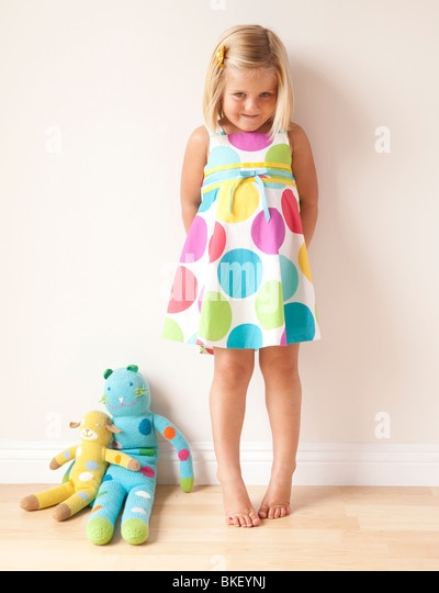 Bashful girl in polka dot dress - Stock Image