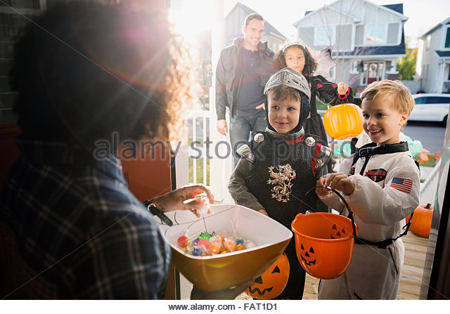Woman with candy greeting trick or treaters - Stock Image