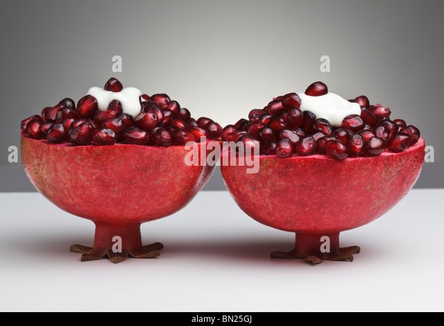 Two cut Pomegranates filled with juicy seeds and topped with Yogurt - Stock Image