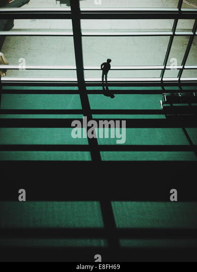 Boy looking out of airport window - Stock Image