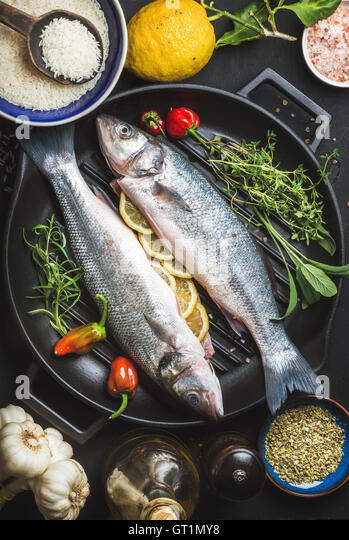 Ingredients for cooking healthy fish dinner. Raw uncooked seabass with rice, lemon, herbs and spices on black grilling - Stock Image
