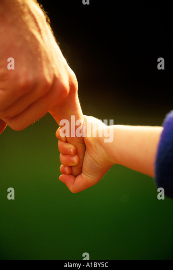 A small child clutches her father s finger during a walk together - Stock Image
