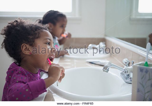 young sisters bruthsing their teeth together - Stock-Bilder
