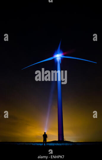 The wind turbine at night in an unusual light- a lonely man shines screw with flashlight . The concept of eco-friendly - Stock-Bilder