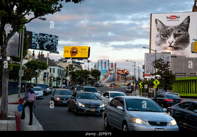 Lit billboards on the Sunset Strip in Los Angeles at dusk. - Stock Image